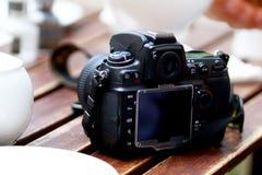 Câmera da foto de DSLR que está na tabela fotografia de stock