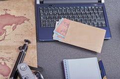 câmera da foto do vintage ao lado de um portátil uma tabuleta um smartphone e um envelope com dinheiro nos euro imagens de stock