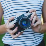 Câmera da foto nas mãos da menina Imagem de Stock Royalty Free