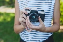 Câmera da foto nas mãos da menina Fotos de Stock Royalty Free