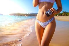 Câmera da terra arrendada da mão da mulher na praia tropical Corpo 'sexy' no roupa de banho foto de stock royalty free