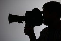 Câmera de filme farpada do homem da silhueta de lado Foto de Stock