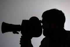 Câmera de filme farpada do homem da silhueta de lado Imagens de Stock