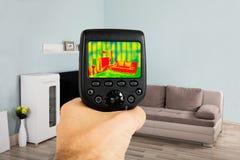 Câmera de Person Hand Using Infrared Thermal na sala de visitas fotografia de stock royalty free