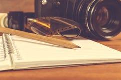 Câmera de SLR na tabela ao lado da tira e do lápis do filme negativo Imagens de Stock