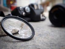 A câmera deixada cair à terra, fazendo com que o filtro quebrem, o len e o corpo danificados No conceito do seguro de acidente so imagens de stock royalty free