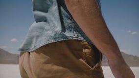A câmera do close-up inclina acima no homem na roupa ocasional que anda ao longo dos planos incríveis do deserto do lago de sal e vídeos de arquivo