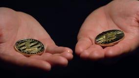 A câmera do close up mostra as palmas com modelos de Bitcoin e de Litecoin video estoque