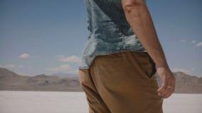 A câmera do close-up segue o homem livre na roupa ocasional que anda avante, olhando em torno do deserto ventoso do lago de sal e vídeos de arquivo