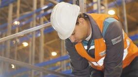 A câmera do movimento lento mostra o trabalhador no capacete e na veste filme