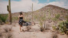 A câmera do movimento lento segue a mulher bonita nova do turista com o vento que funde no vestido que explora o deserto grande d filme