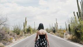 A câmera do movimento lento segue a mulher feliz bonita nova do turista que anda ao longo da estrada ensolarada do deserto com o  video estoque