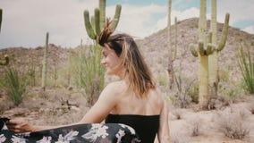 A câmera do movimento lento segue a mulher feliz de sorriso nova do turista com o cabelo do voo que anda no deserto ensolarado ép vídeos de arquivo