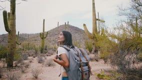 A câmera do movimento lento segue a mulher feliz nova do turista com a trouxa que explora o deserto grande do cacto do Saguaro no video estoque