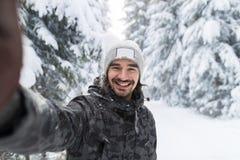 Câmera do sorriso do homem novo que toma a foto de Selfie na neve Forest Guy Outdoors do inverno fotos de stock royalty free