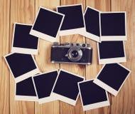 Câmera do vintage e muitos quadros vazios da foto na tabela de madeira alto Fotos de Stock Royalty Free