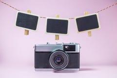 Câmera do vintage e Pegs de roupa pequenos vazios dos quadros-negros acima no fundo do rosa pastel Foto de Stock Royalty Free