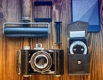 Câmera do vintage, medidor de exposição e uma outra caça com armadilhas da fotografia do filme mesa do ` s do fotógrafo foto de stock