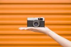 Câmera do vintage na palma fêmea isolada no amarelo imagem de stock