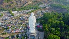 A câmera do zangão pendura acima da estátua gigante da Buda contra a cidade video estoque