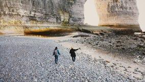 A câmera do zangão segue o homem feliz e a mulher do turista que andam ao longo de Pebble Beach grande bonito às rochas majestosa filme