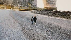 A câmera do zangão segue os pares românticos felizes do turista que andam ao longo de surpreender Pebble Beach às rochas brancas  vídeos de arquivo