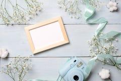 Câmera e moldura para retrato da foto na tabela de madeira azul Quadro mínimo das flores da mola, cores pastel, estilo colocado l foto de stock
