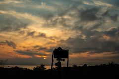 Câmera e nascer do sol sobre a represa de Nakharin do si foto de stock