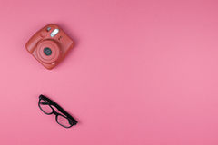 Câmera e vidros em um fundo cor-de-rosa Forma do conceito parte superior vi Imagem de Stock Royalty Free