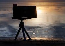 A câmera em um tripé remove o por do sol Imagem de Stock