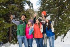 Câmera esperta do telefone da posse do homem que toma o inverno de Forest Young People Group Outdoor da neve da foto de Selfie Fotos de Stock