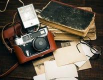 Câmera imóvel retro e algumas fotos velhas no fundo de madeira da tabela Foto de Stock Royalty Free