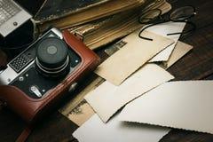 Câmera imóvel retro e algumas fotos velhas no fundo de madeira da tabela Fotos de Stock Royalty Free