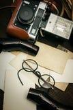 Câmera imóvel retro e algumas fotos velhas no fundo de madeira da tabela Fotografia de Stock