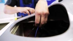 A câmera mostra as mãos do homem usando alicates diagonais para cortar fios azuis filme