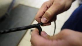 A câmera mostra as mãos do homem usando-se colocando o fio preto no cabo espiral longo filme