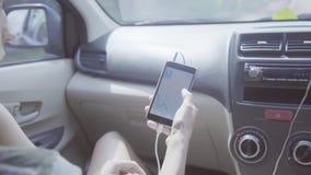 A câmera mostra a jovem mulher com o smartphone no carro, então indivíduo de cabelos compridos bonito vídeos de arquivo