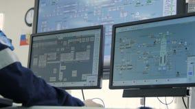 A câmera mostra monitores e homem da opinião da parte traseira no computador