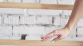 A câmera mostra o movimento suave da dança da mão do ` s da mulher no fundo branco da parede filme