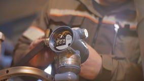 A câmera mostra o trabalhador que torce a porca com chave no medidor da pressão filme