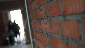 A câmera mostra a parede com tijolos vermelhos e concreto e silhuetas cinzentos dos homens video estoque