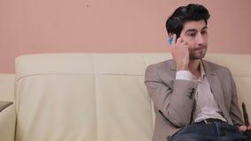 A câmera move-se da direita para a esquerda e toma-se um homem de negócios novo que fala no telefone vídeos de arquivo