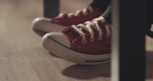 A câmera move-se do direito para a esquerda e decola-se enquanto os pés nas sapatilhas vermelhas batem fora video estoque