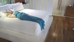 A câmera move-se em quartos sobre a mulher delgada nova que dorme em uma cama vídeos de arquivo