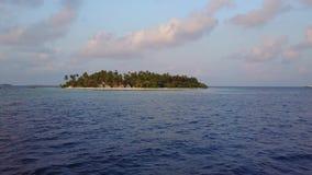 A câmera move-se longe do hotel de resort da ilha tropical redondo do atol com as palmeiras brancas da areia sobre o indiano de t video estoque