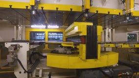 A câmera move-se para quatro janelas quadradas para a máquina de corte da imprensa, preparação para fazer o corpo de carro filme