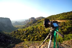 Câmera no tripé pronto para tomar imagens do por do sol entrante em Meteora imagem de stock