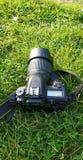 Câmera preta de DSLR em um campo de grama imagem de stock