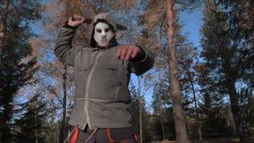 Câmera que focaliza no homem na máscara assustador de Dia das Bruxas que que usa o machete filme