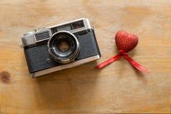 Câmera retro com corações vermelhos em um de madeira Fotos de Stock